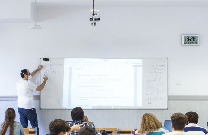 Lecturer teaching at Comillas Pontifical University. He is wearing a facemask and the class are sat socially-distanced. A Sony remote camera and Beamforming Microphone are visible, suspended from the ceiling.