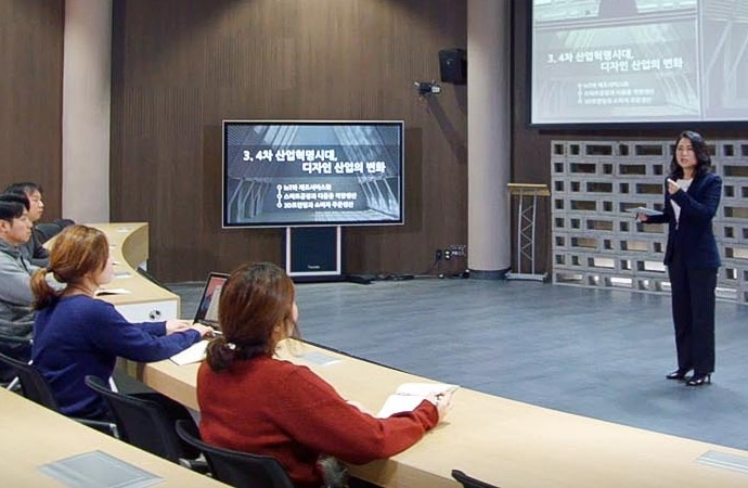 A lecturer presents before a hall full of students at the Cyber University of Korea