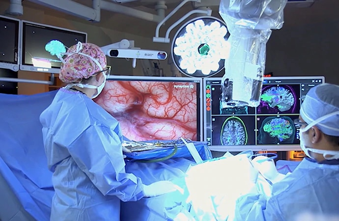 Surgeons looking at feed from a robotic digital microscope on Sony's 55 inch 4K display
