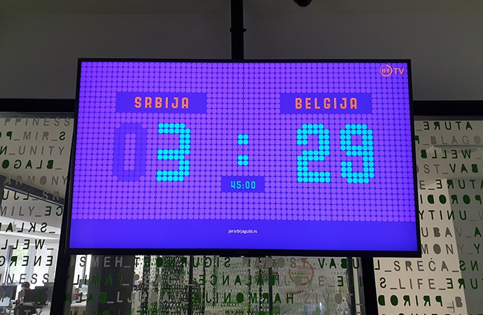 BRAVIA display showing time on the screen with letter behind on the wall
