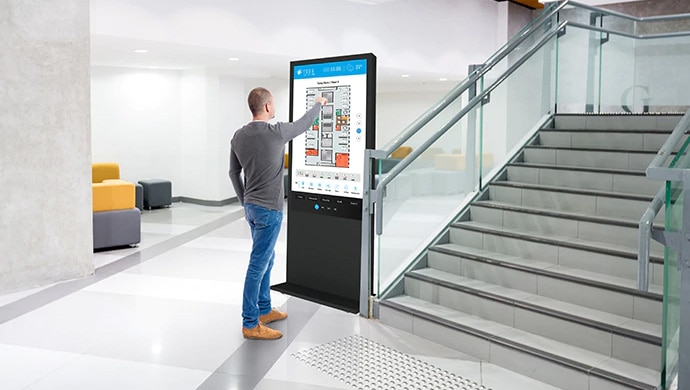 Man interacting with a touch-screen professional display, displaying office information driven by TEOS.