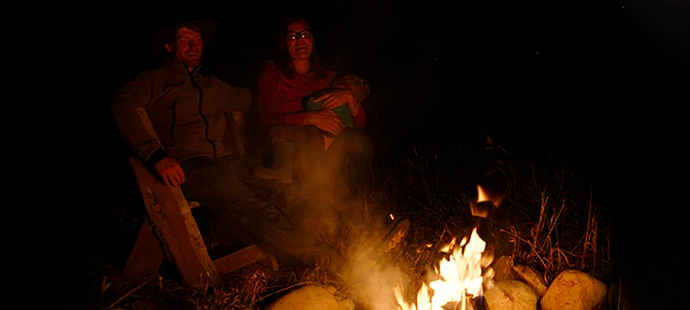 A family gathered around a fire at night illustrates how ISO 2500 allows for acquiring detail in low lighting conditions.