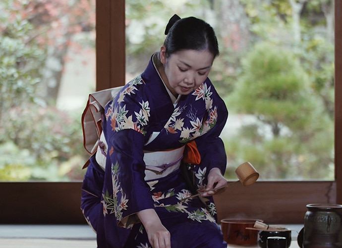 Japanese woman in traditional dress preparing tea