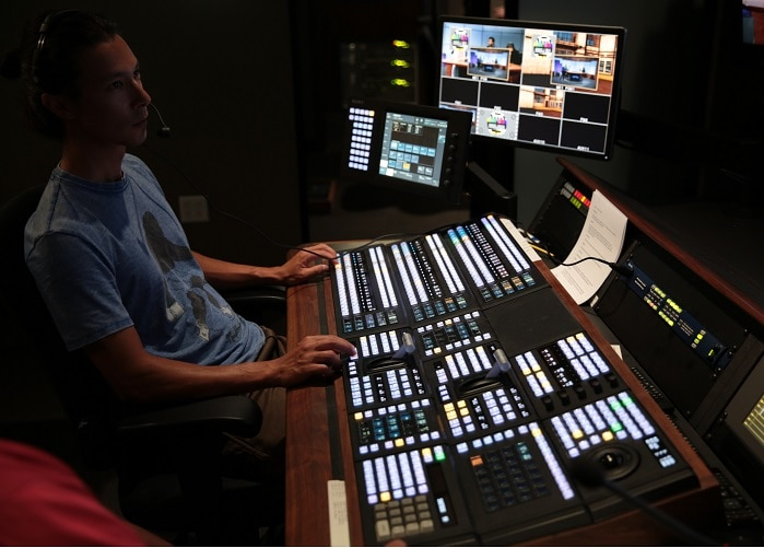 Man operates AV mixing desk in KLCS Control Room. He is seated at extreme left of image, with the desk and controls in front of him. View #3.