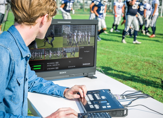 man using MCX-500 to stream American football game