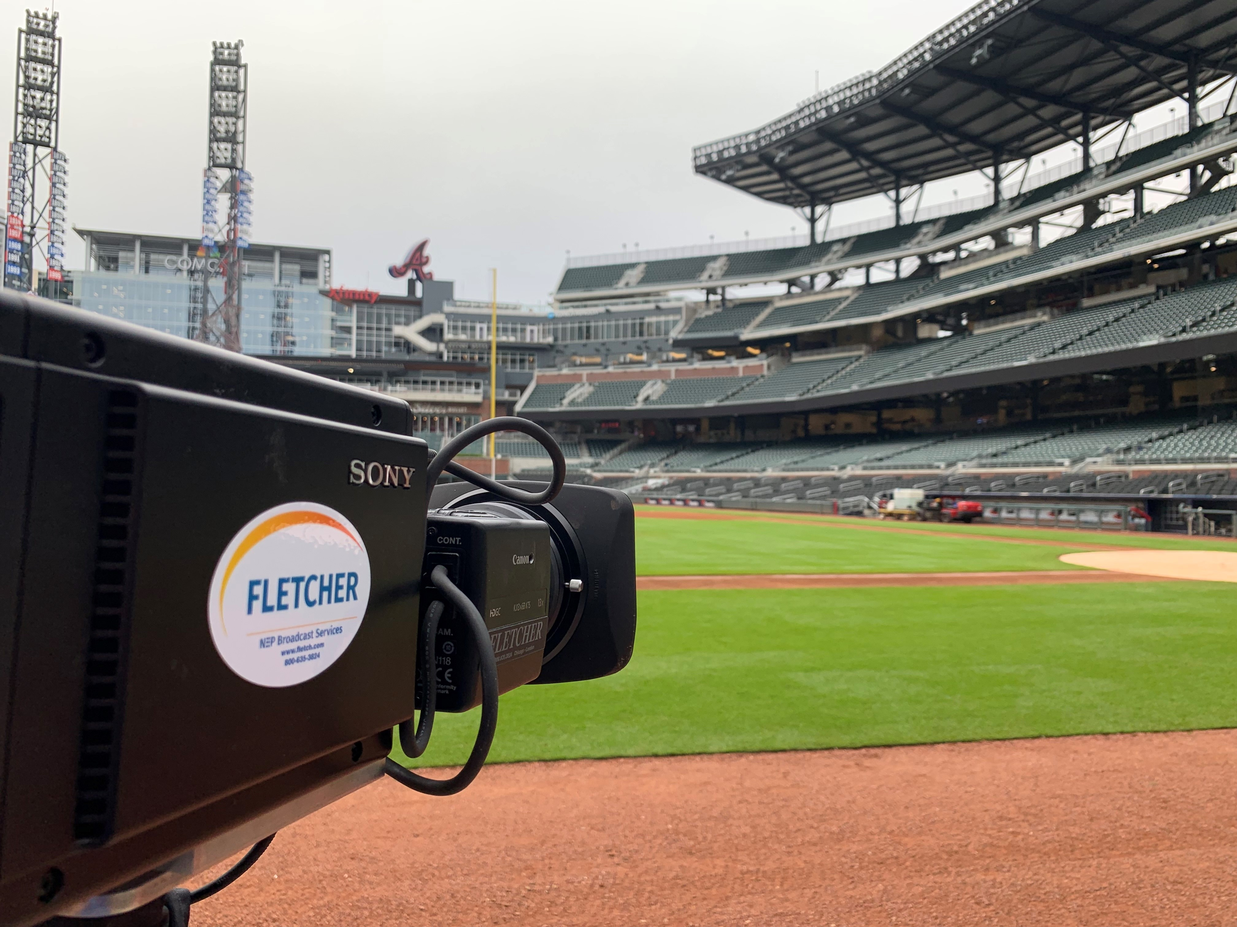 A Sony HDCV-P50 camera, sporting a white oval Fletcher sticker, sits outside, low on the outfield at a baseball stadium. The camera is at extreme left, facing across the field to the right, and away from the viewer. View #1.