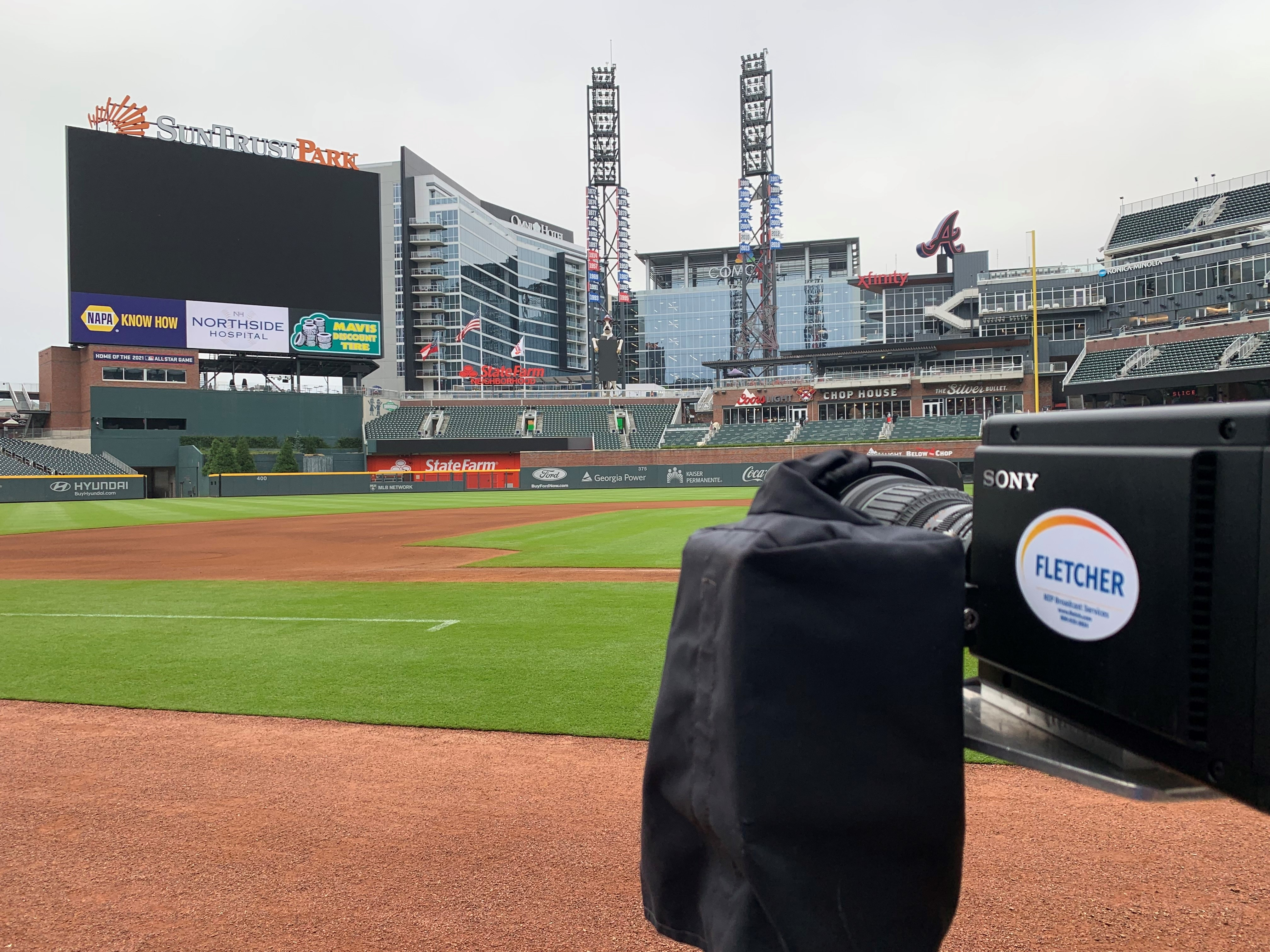 A Sony HDCV-P50 camera, sporting a white oval Fletcher sticker, sits outside, low on the outfield at a baseball stadium. The camera is at extreme right, facing across the field to the left, and away from the viewer. View #2.