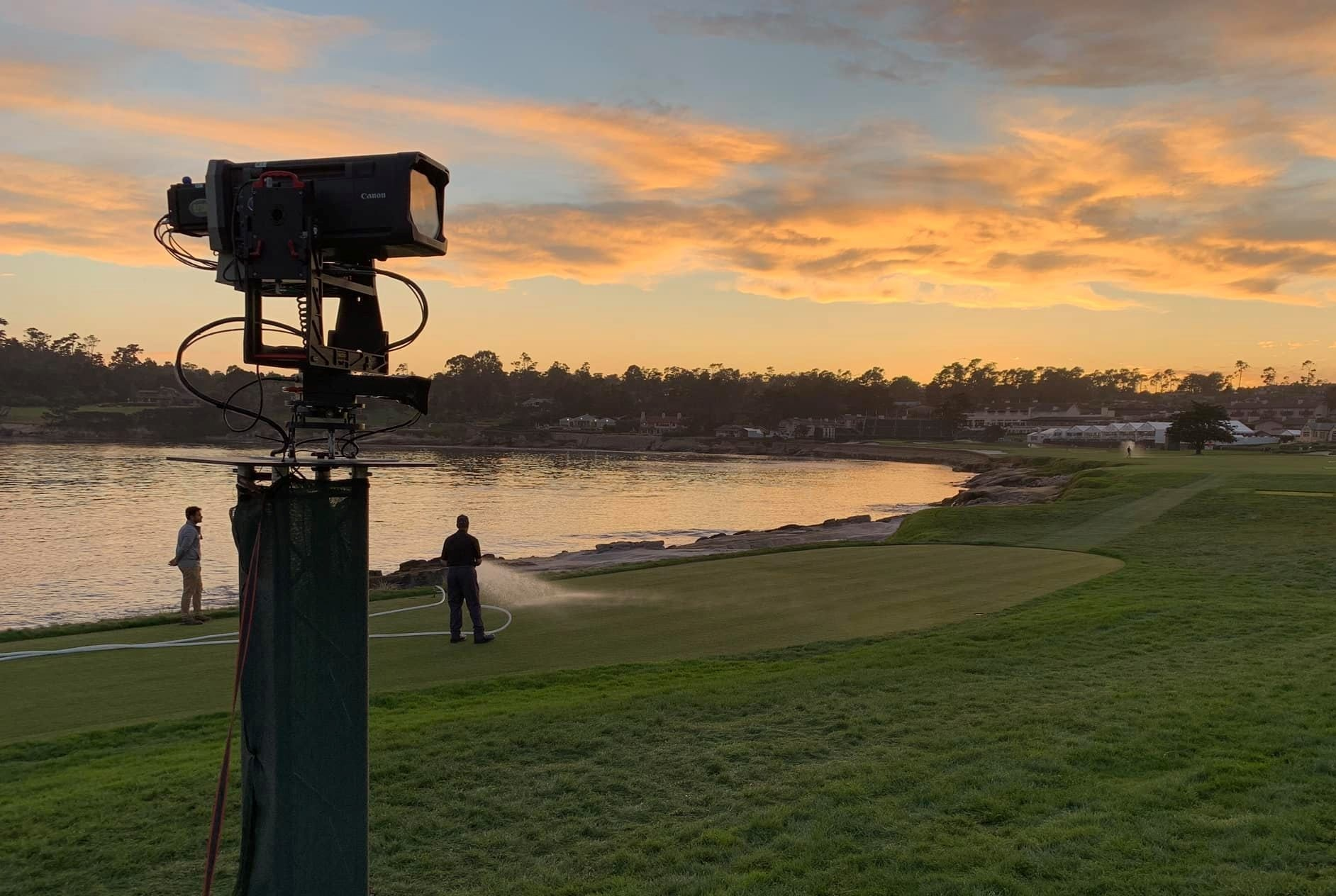A view of a lake at sunset, at Pebble Beach golf course, Monterey County, California, US. The horizon is a heavy tree line at mid-frame, with a lake reflecting the sunset at mid-left of the image. A security camera on a pylon rises vertically in the foreground.