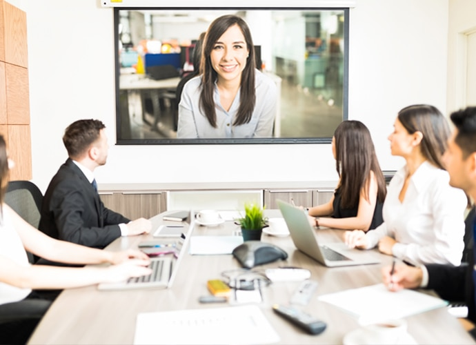 A small group of 5 people are sat around a table in an office looking at a screen which is projecting a video conference of a woman