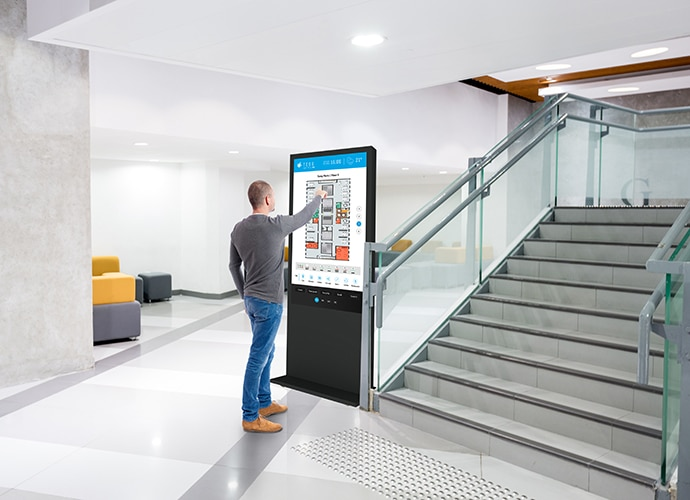 Image showing a man interacting with a digital map of an office, powered by TEOS.
