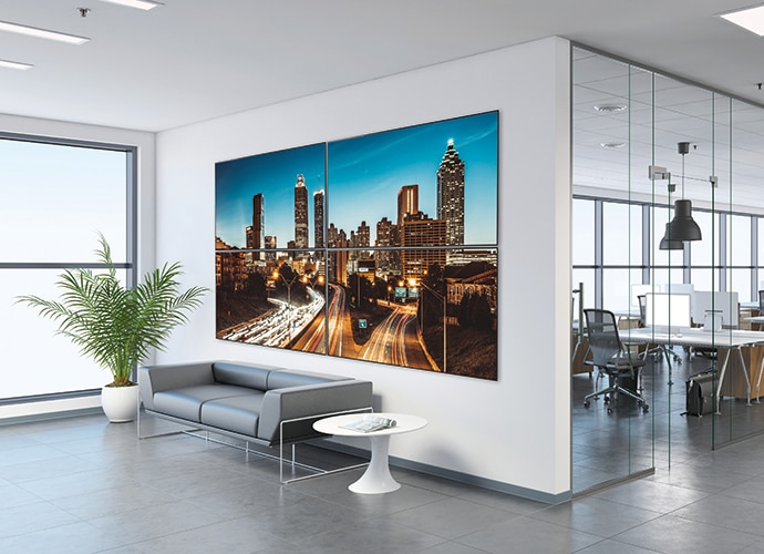Image showing digital signage within a lobby of a workplace, depicting a city skyline image.
