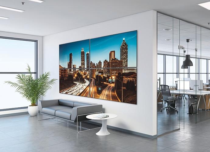 Bir iş yerinin lobisinde, şehir manzarası gösteren bilgi ekranının görüntüsü.