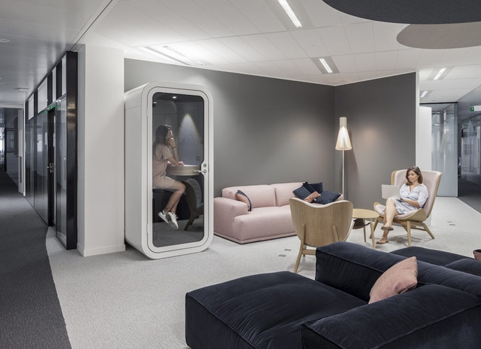 A communal area at Capgemini. A woman takes a phone call in a privacy pod, while another works on her laptop in an armchair.