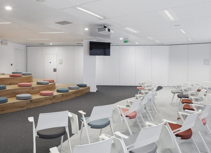 A small corporate auditorium with a BRAVIA screen and informal seating.