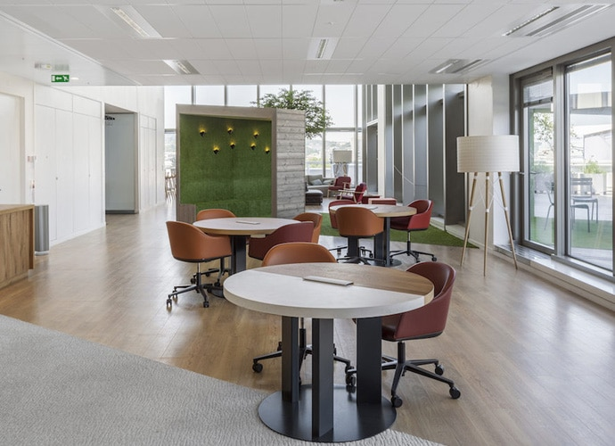 A breakout space with tables of four chairs equally spaced and large glass windows.
