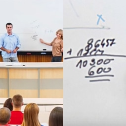 A lecture hall with two presenters in front of a whiteboard.