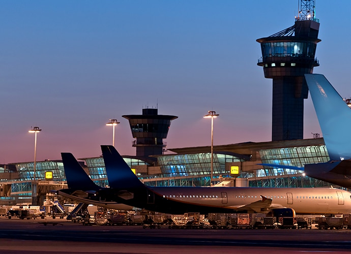 Illustrative image showing an airport at night with plnes parked in the termac