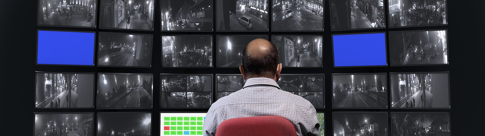 Man viewing video feed from security camera on a multi screen display