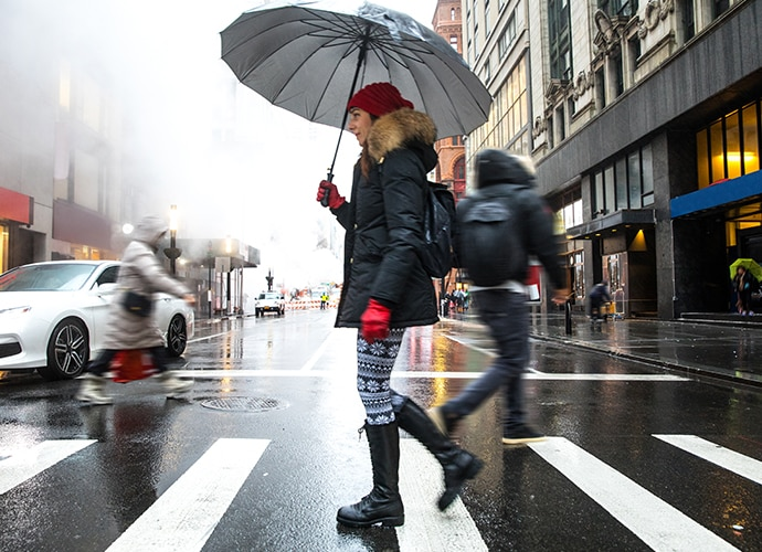 A woman stepping into a street holding an umbrella