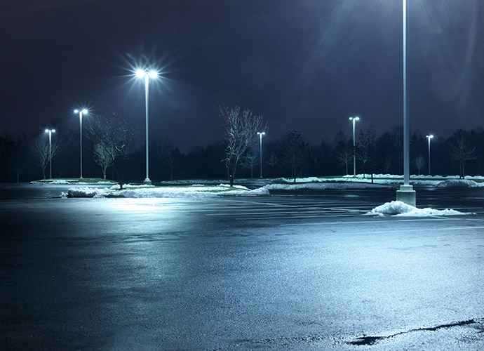 An empty parking lot at night with snow piled on the sides