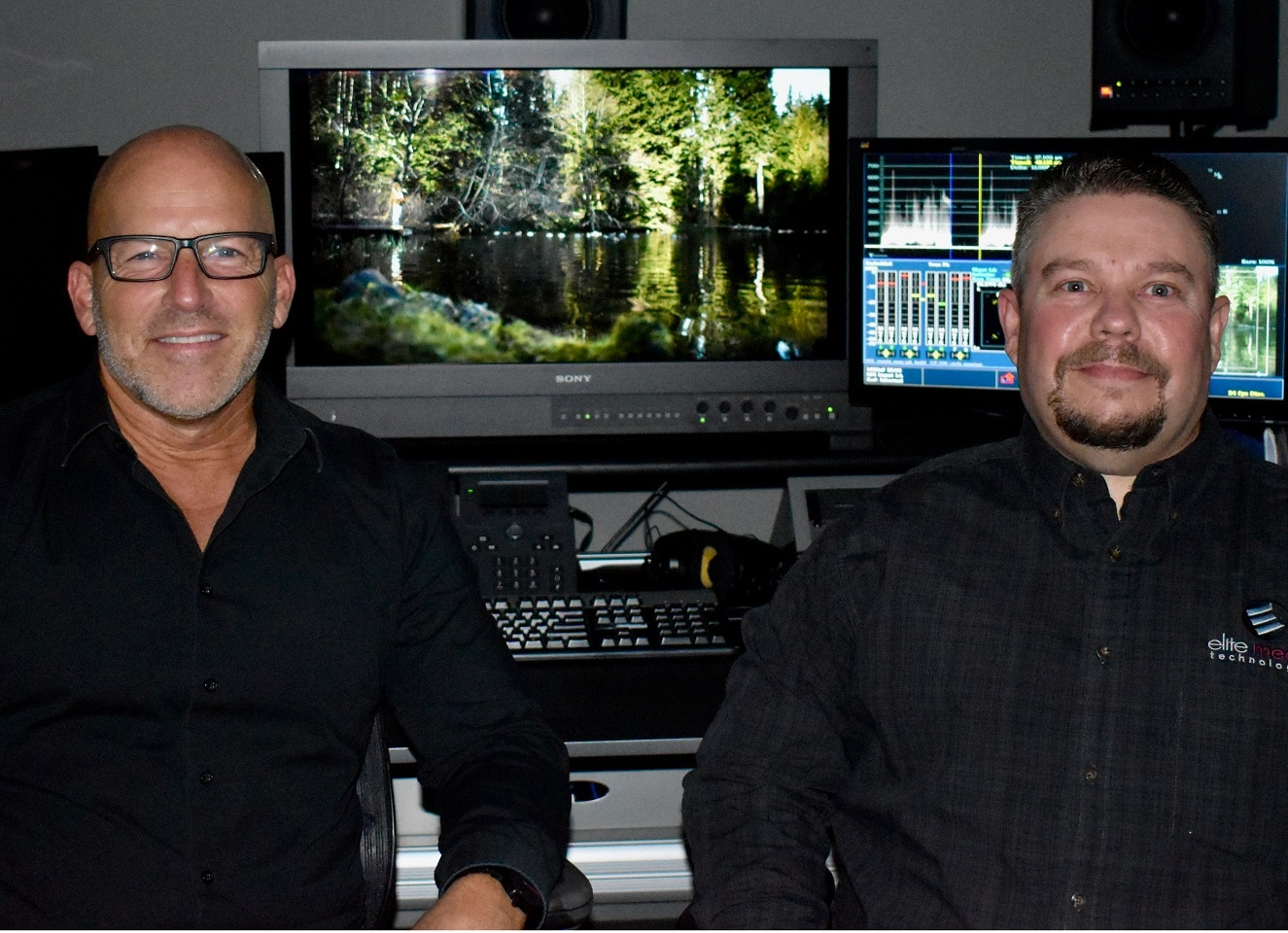 Interior of Elite Media AV suite. Rear view of Jason Altman and Nick Mairose, operating a video mixing desk.