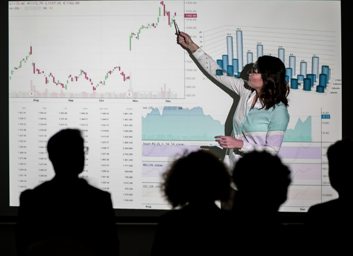 Woman presenting data to an audience.