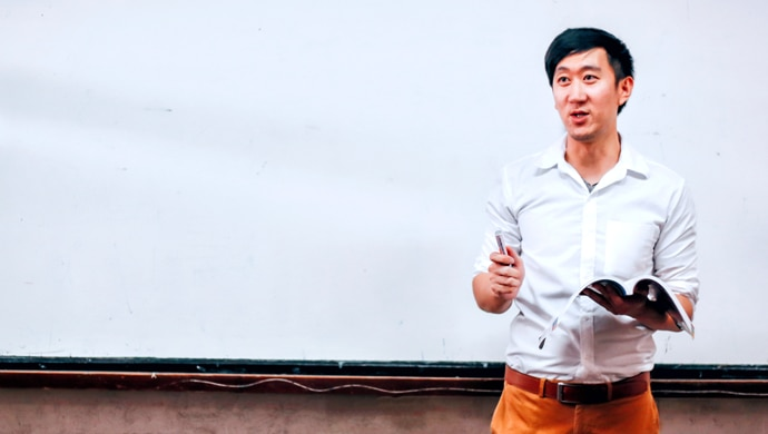 Man stood up, lecturing a class.