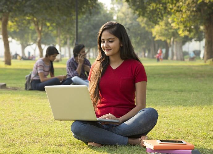 Una estudiante sentada al aire libre sobre la hierba mientras participa en una sesión de aprendizaje online en su portátil