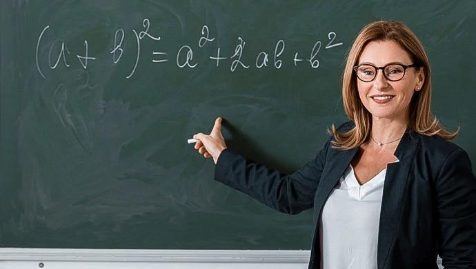 Una profesora de pie frente a una pizarra