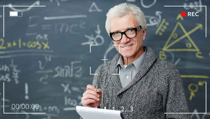 A lecturer is stood in front of a blackboard with various equations. There is an image overlay, illustrating that he is being recorded by a camera.