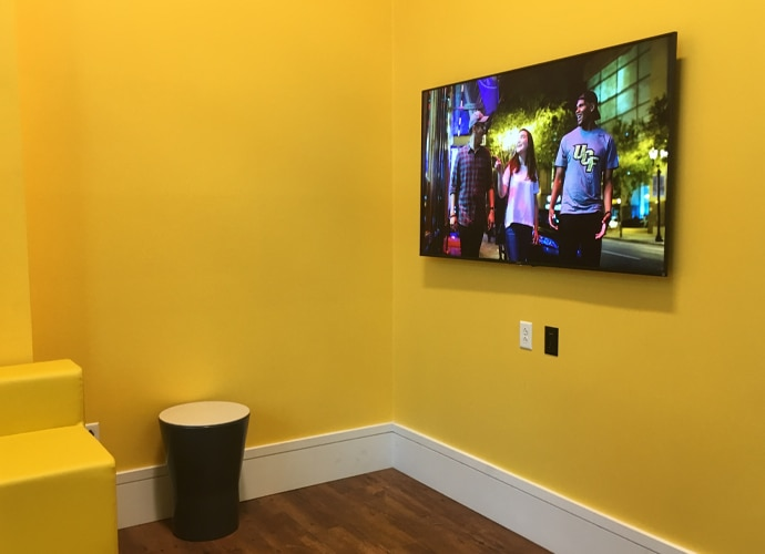 Image showing the interior of another breakout room, showing a UCF-themed image on the BRAVIA monitor.