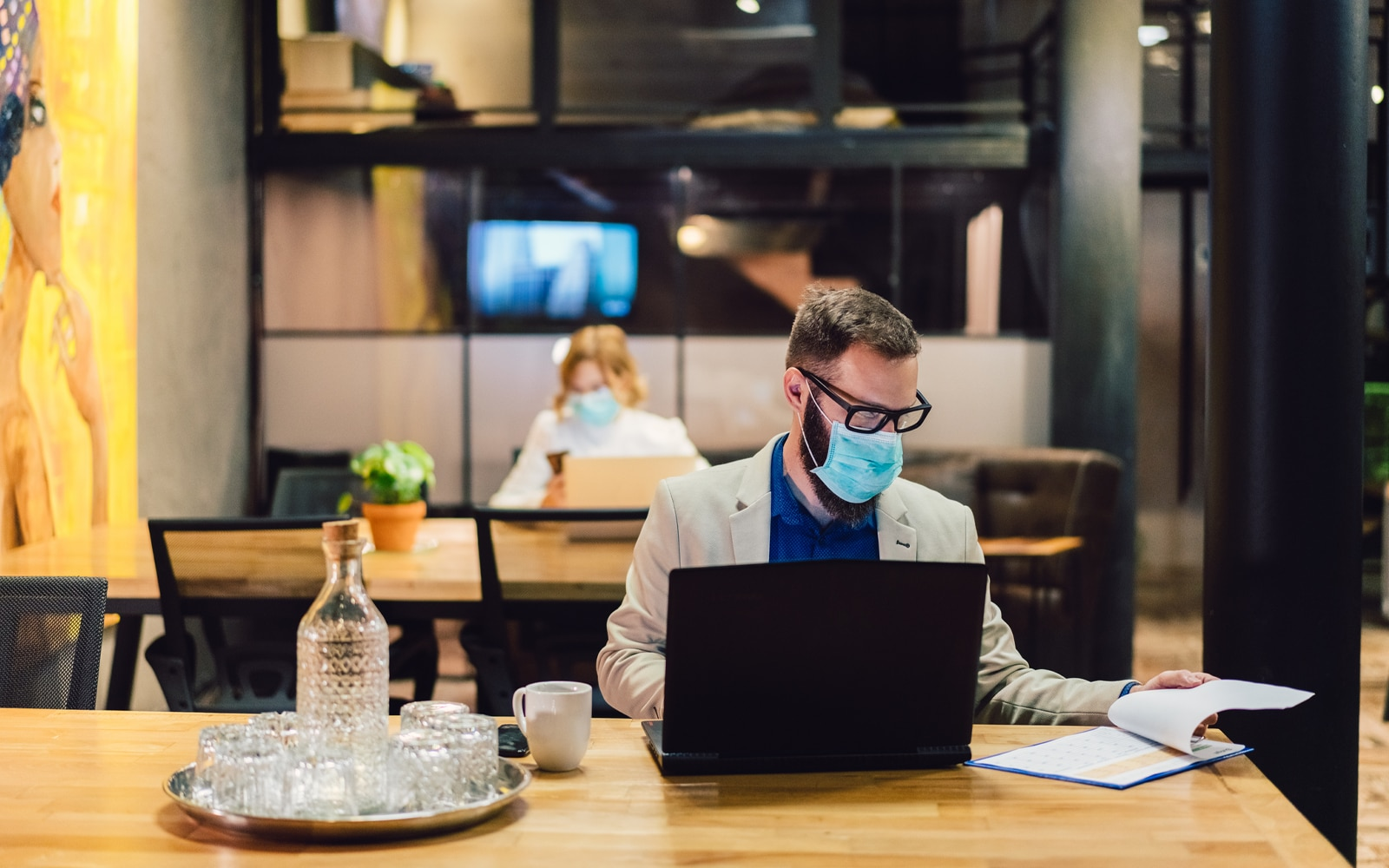 A man working at a desk, with a laptop, notepad and cup of coffee in front of him. He is wearing a facemask. In the background you can see a woman sat far away looking at a phone, complying with social distancing.
