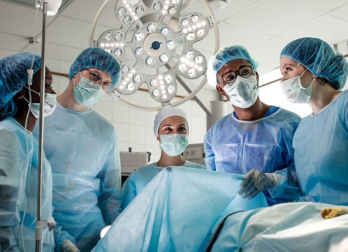 Surgeons looking at two boom-arm mounted LMD-X3200MD displaying a surgical image in a brightly lit operating room