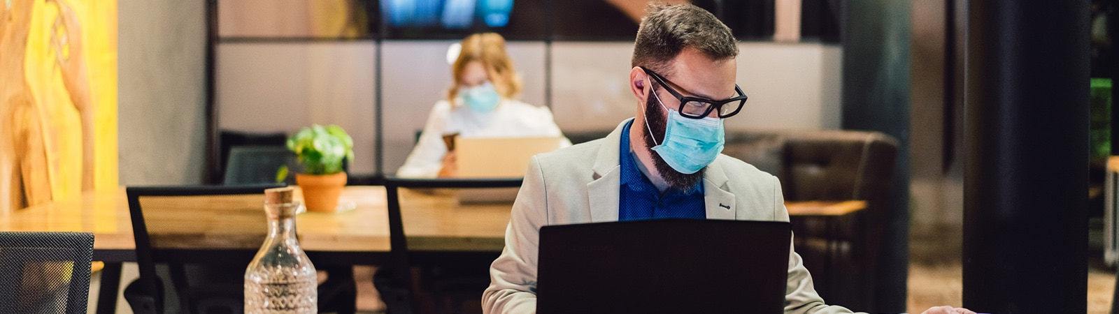 A man wearing a mask working in a social distanced office with his laptop