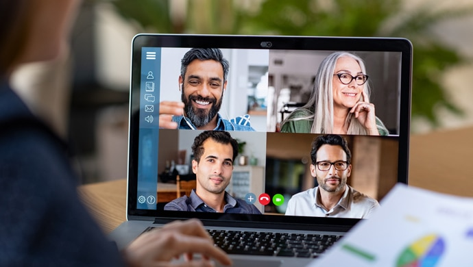 A laptop screen at a home desk showing four users on a video call together