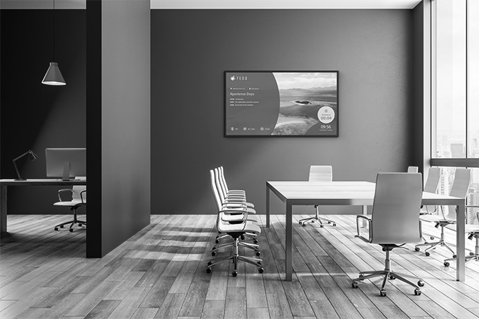An empty office room with a BRAVIA professional display situated behind a table and chairs.