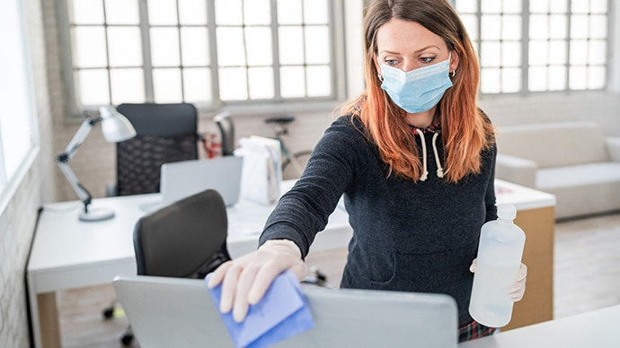 A woman wearing a mask cleaning her desk using a cloth and disinfectant in the office.