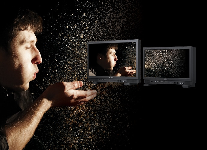Image showing a man is blowing dust on his hand, product shot of PVM-X2400/X1800 on the right-hand side