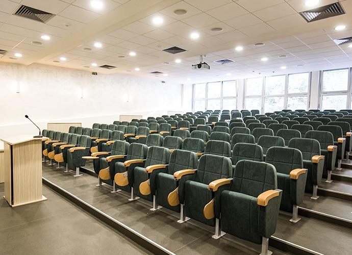 Sala wykładowa średniej wielkości zprojektorem zamontowanym pod sufitem.