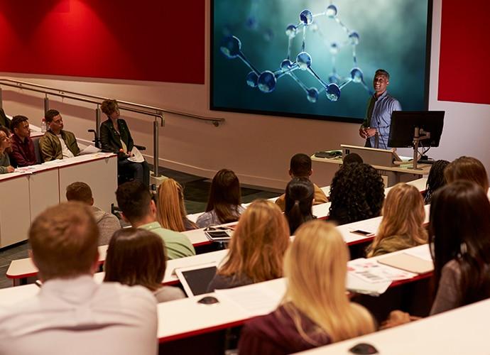 Mężczyzna wygłaszający prelekcję przed publicznością.