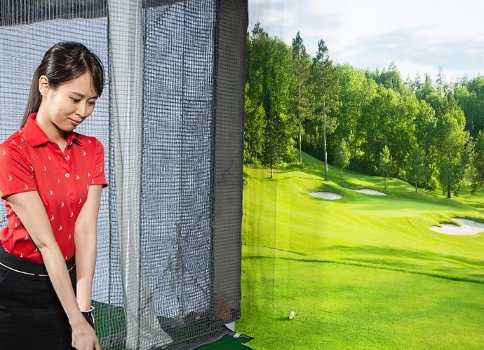 Zdjęcie przedstawiające symulator golfa. Kobieta wykonuje wymach kijem golfowym.