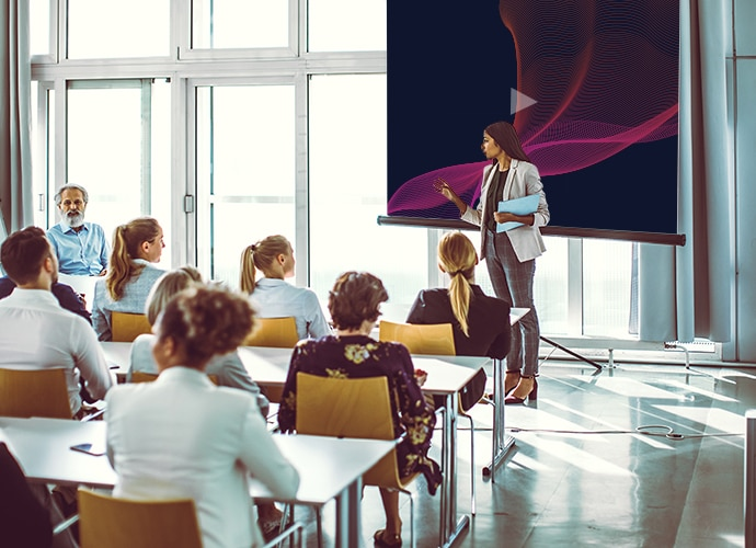 A woman is stood in front of an audience, presenting dynamic video content.