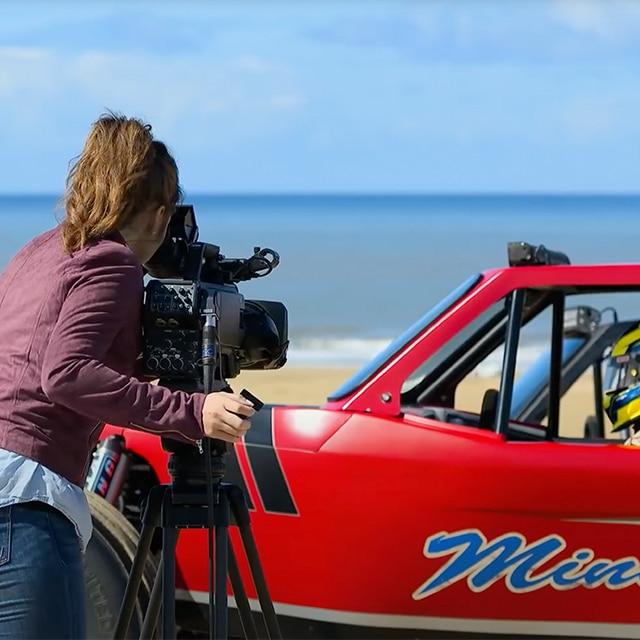 Une femme regarde une voiture à travers un appareil photo professionnel