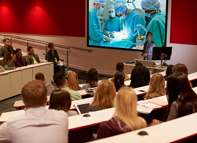 Students in an auditorium looking at surgery in progress on a projector