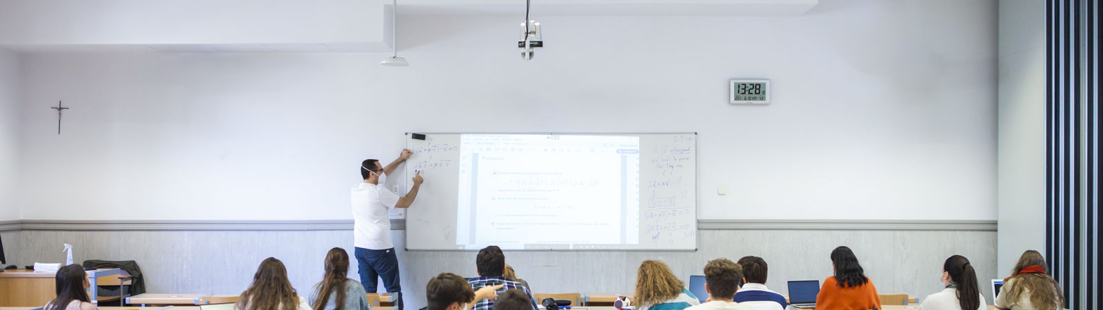 A teacher is presenting in front of a socially-distanced classroom. The Beamforming Microphone and PTZ camera is visible, suspended from the ceiling.
