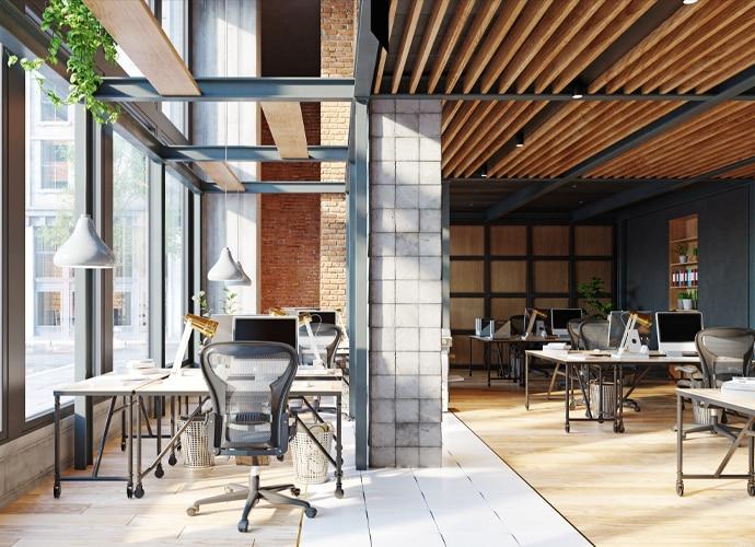 Yüksek tavanlı aydınlık bir ofiste beyaz masalar ve döner büro sandalyeleri.