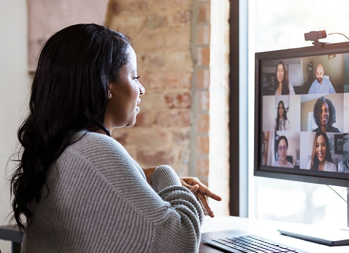 Woman speaking with her collogues from home using a webcam