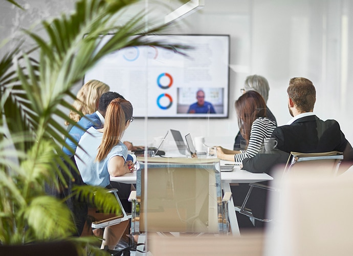 People working in a meeting room and hosting a call on the screen with a remote worker