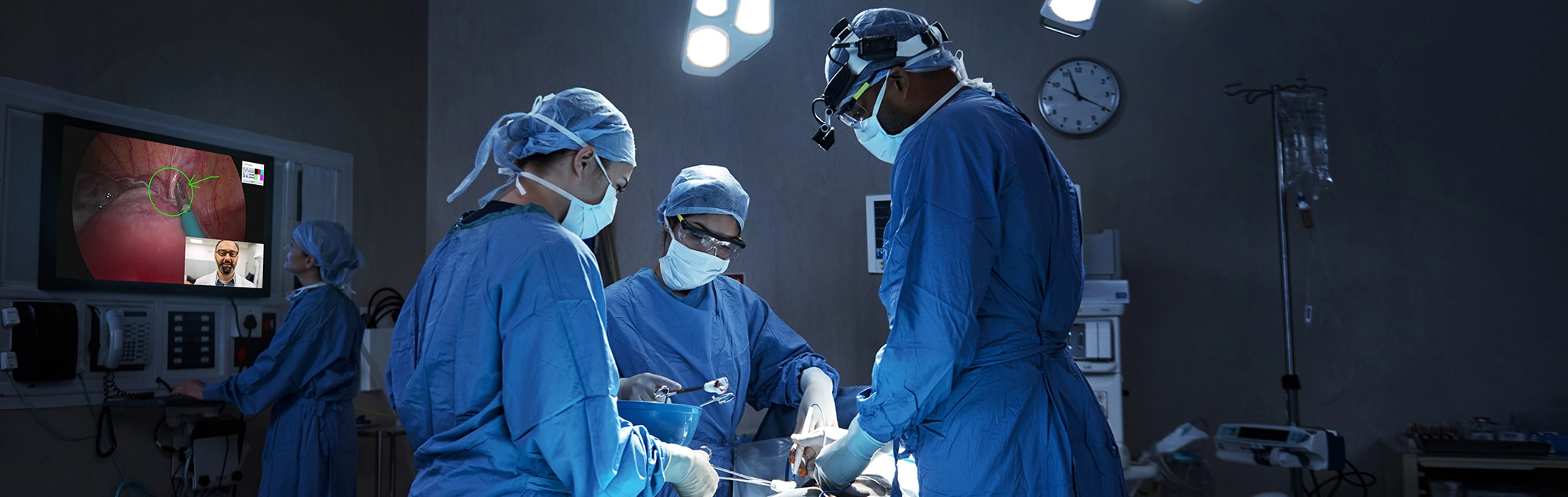 A surgeon having a remote consultation with a colleague through a wall mounted display while a surgery is in progress in the OR