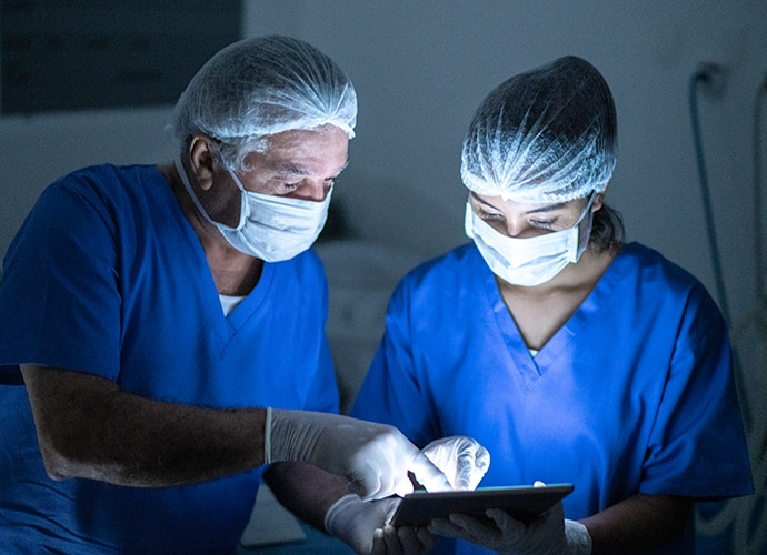Two masked surgeons pointing at a tablet screen while speaking